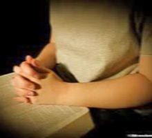 mujer poniendo sus manos en una Biblia